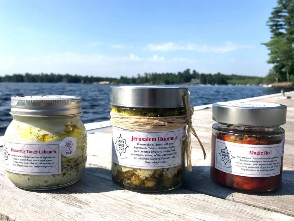 3 jars -- hummus, labaneh, red peppers -- stacked with lake behind - July 2020